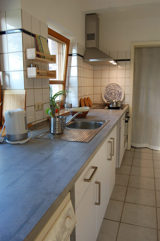 Blick in die vollausgestattete Küche. Im Hintergrund der großzügige Abstellraum